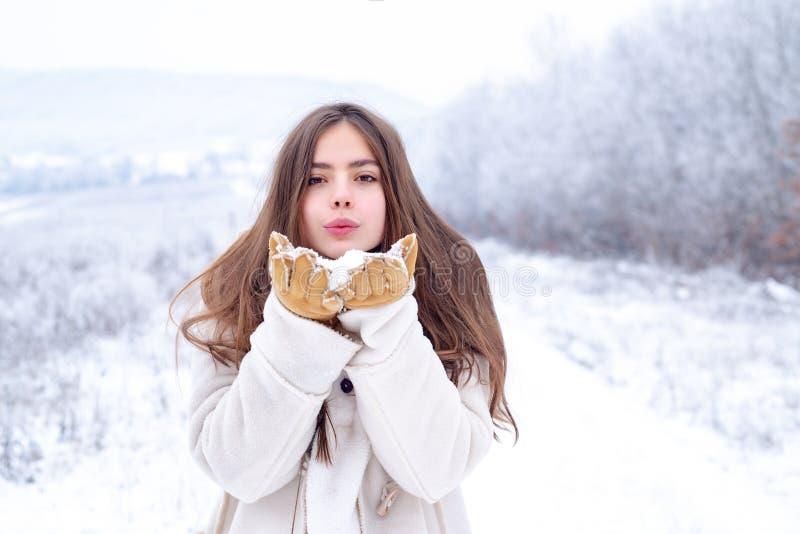 Förälskelsevinter Den lyckliga kalla flickan som blåser röda kanter, gör för att lufta kyssen som bär en vit tröja över snöig bak arkivfoton