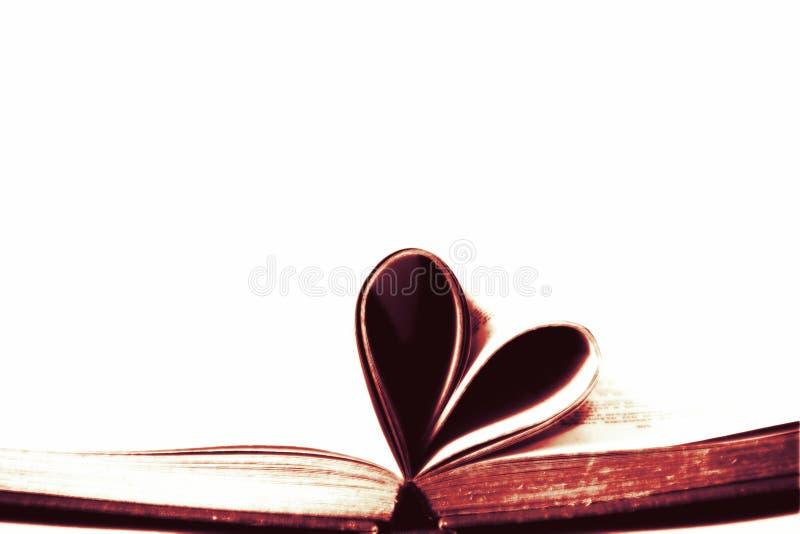 Föråldrad gammal bok med sidor som formas in i hjärtaformsymbol med tom vit isolerad kopieringsutrymmebakgrund arkivfoton