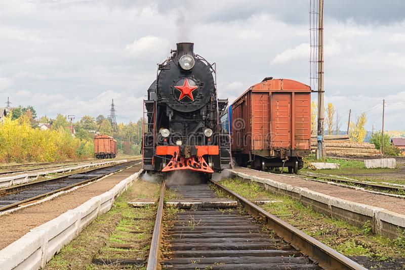 För ångalokomotiv för tappning svart drev med vagnar på station arkivbild