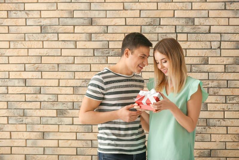 För öppningsgåva för ung kvinna ask från hennes pojkvän nära tegelstenväggen royaltyfria bilder