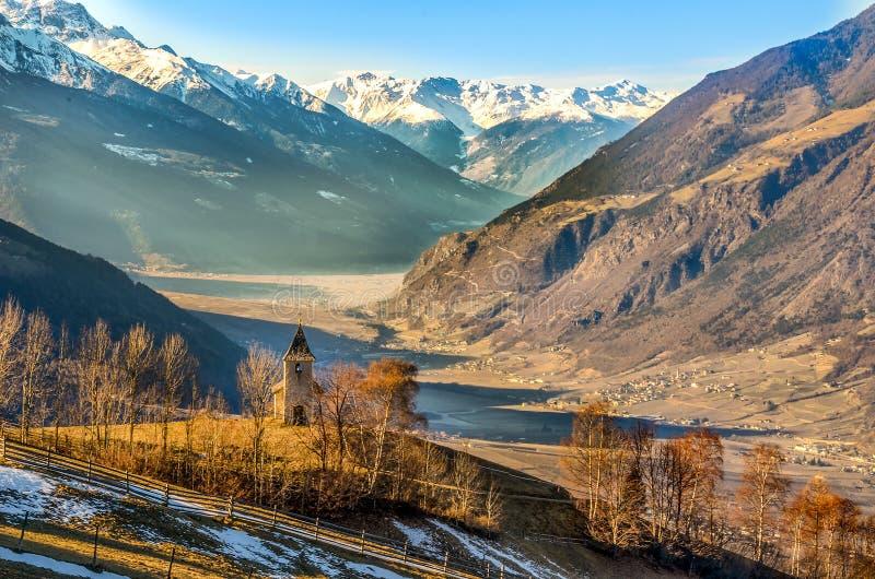 För adige för panoramatrentino alt- vinter för berg för kyrka val venosta fotografering för bildbyråer