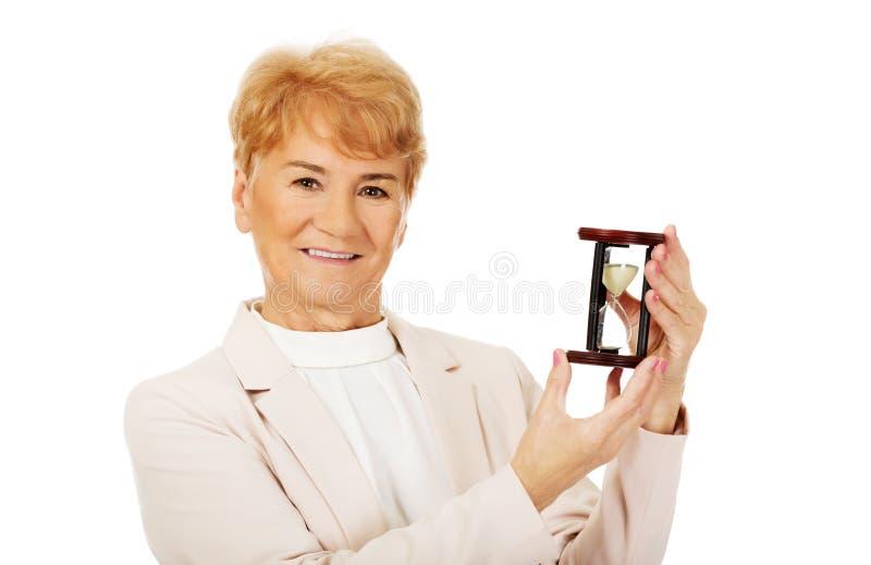 För affärskvinna för leende äldre hållande sandglass arkivfoton