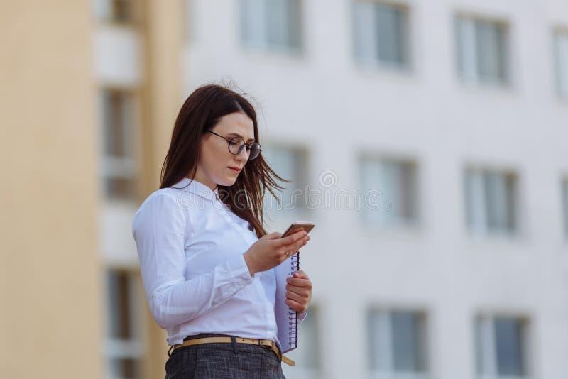 För affärskvinna för stående ung bärande vit skjorta genom att använda dörrar för smartphone ut Kvinnligt läsningsmsmeddelande, i royaltyfri bild
