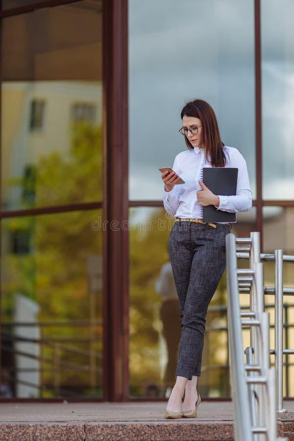 För affärskvinna för stående ung bärande vit skjorta genom att använda dörrar för smartphone ut Kvinnligt läsningsmsmeddelande, i arkivfoto