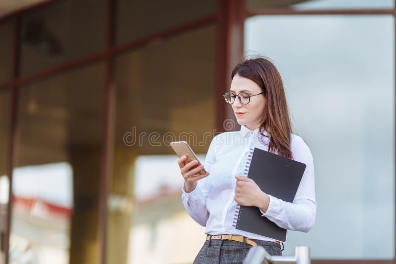 För affärskvinna för stående ung bärande vit skjorta genom att använda dörrar för smartphone ut Kvinnligt läsningsmsmeddelande, i arkivbilder