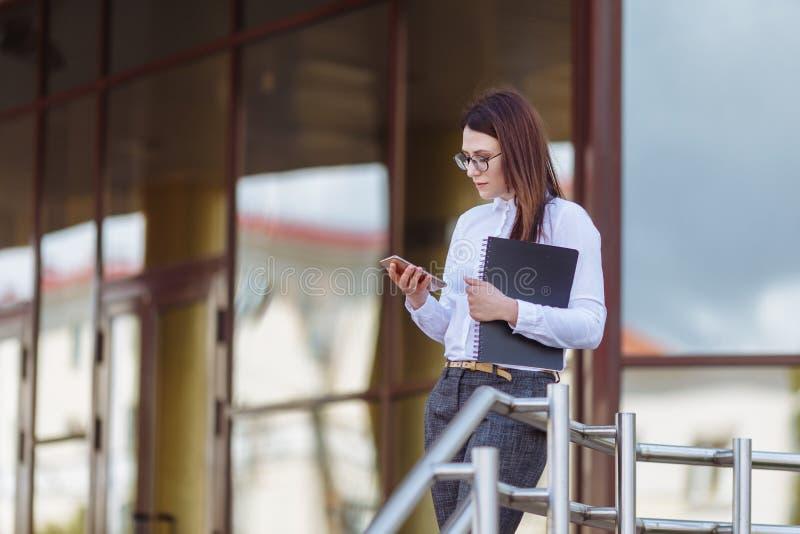 För affärskvinna för stående ung bärande vit skjorta genom att använda dörrar för smartphone ut Kvinnligt läsningsmsmeddelande, i royaltyfri foto