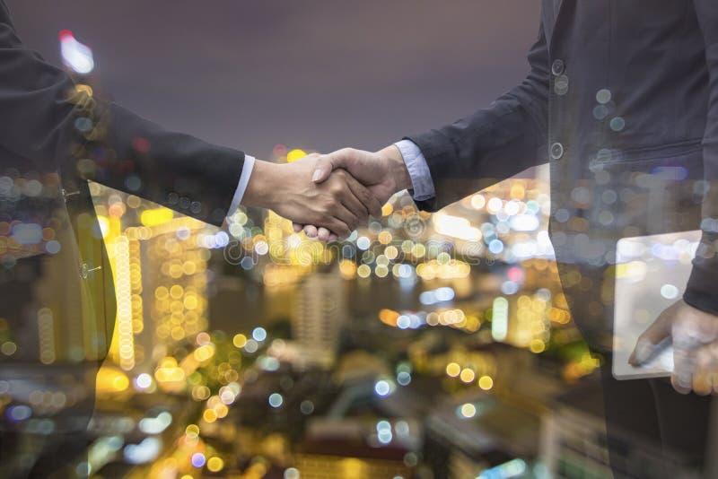 för affärsmanskaka för dubbel exponering hand och nattstad, handskakning royaltyfria bilder