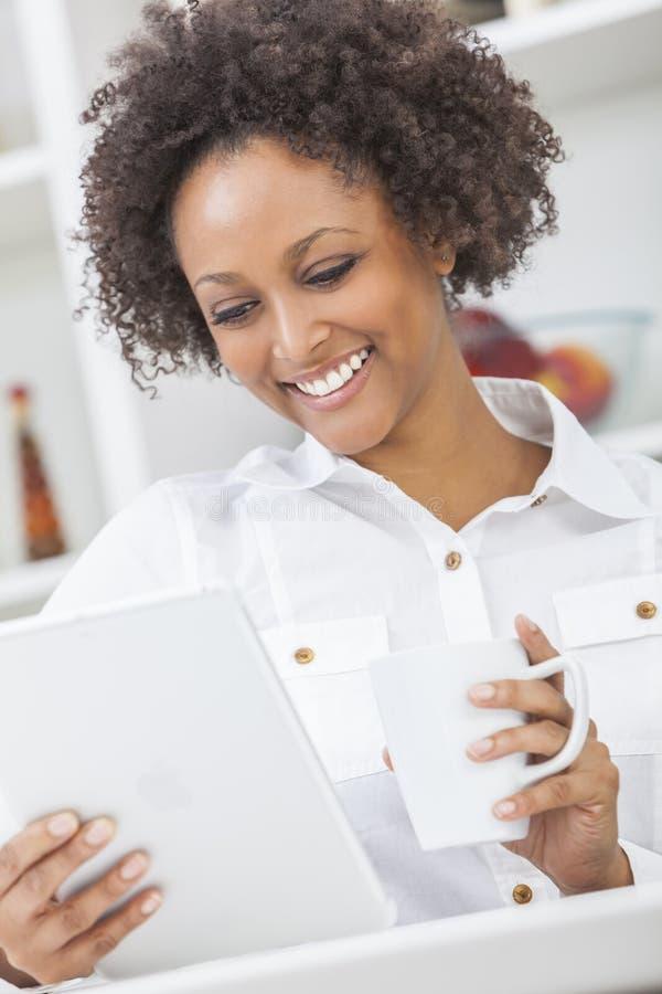 För afrikansk amerikanflicka för blandat lopp dator och kaffe för minnestavla arkivfoton
