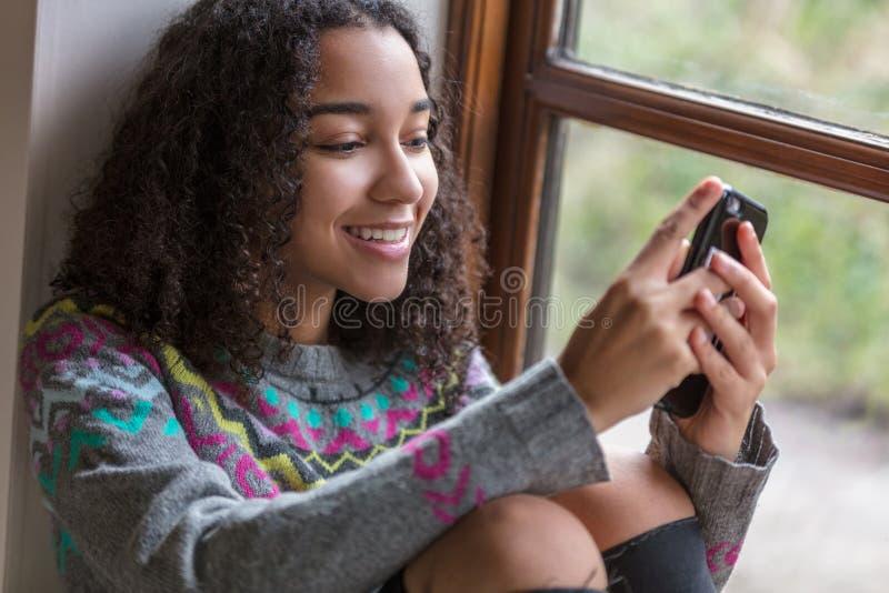 För afrikansk amerikanflicka för blandat lopp tonåring på mobiltelefonen arkivbilder