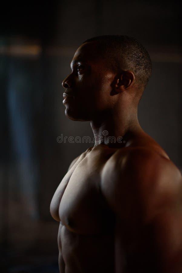 För afrikansk amerikankondition för man tränga sig in den svarta visningen för modell i studio med mörk bakgrund royaltyfri foto