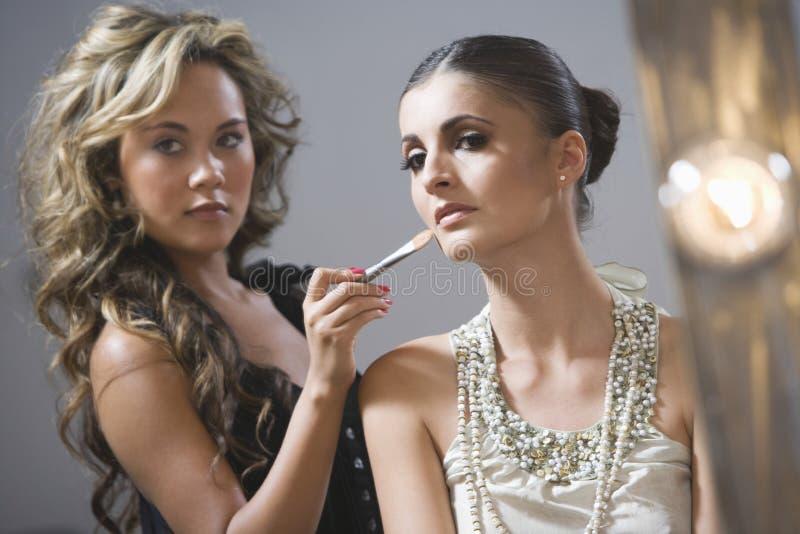 För Applying Foundation To för makeupkonstnär modell mode arkivbild