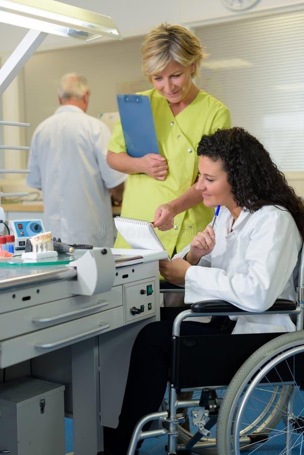 F?r arbetsledarevisning f?r tand- tekniker anm?rkning till den handikappade allm?ntj?nstg?rande l?karen royaltyfria foton