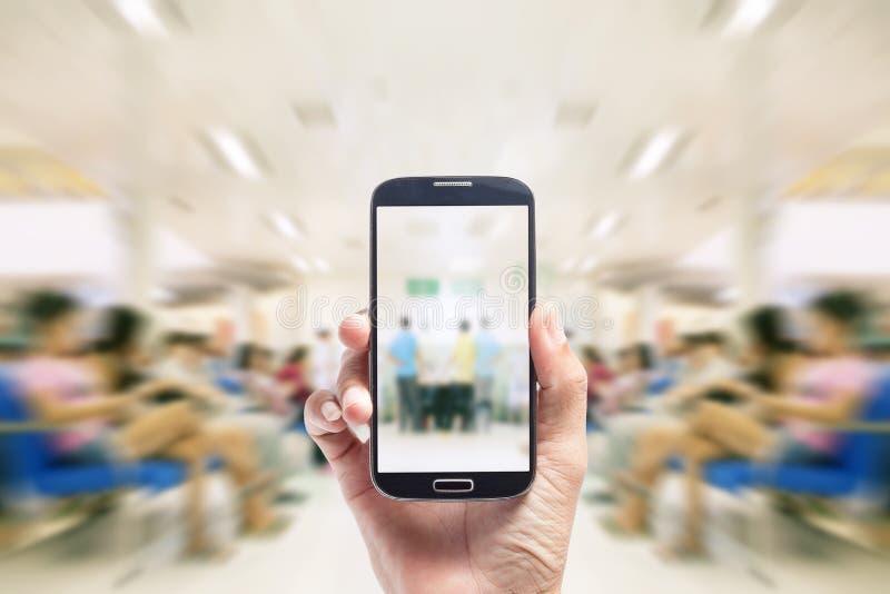 För asiatisk smart telefon handhåll för man, på suddig bakgrundspatient w royaltyfri bild