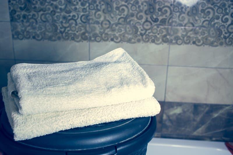 För bakgrunds- och vitbrunnsort för suddigt badrum inre handdukar på marmor royaltyfri bild