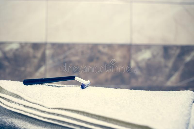 För bakgrunds- och vitbrunnsort för suddigt badrum inre handdukar på marmortandborsterakkniven arkivfoton