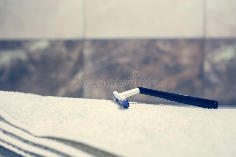 För bakgrunds- och vitbrunnsort för suddigt badrum inre handdukar på marmortandborsterakkniven royaltyfri foto