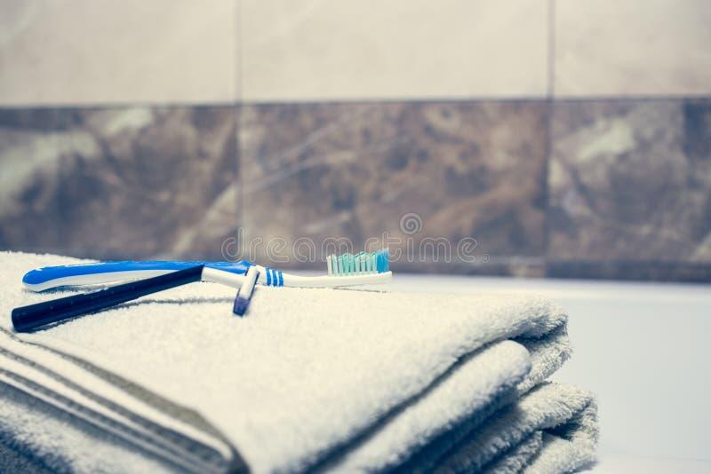 För bakgrunds- och vitbrunnsort för suddigt badrum inre handdukar på marmortandborsterakkniven arkivbild