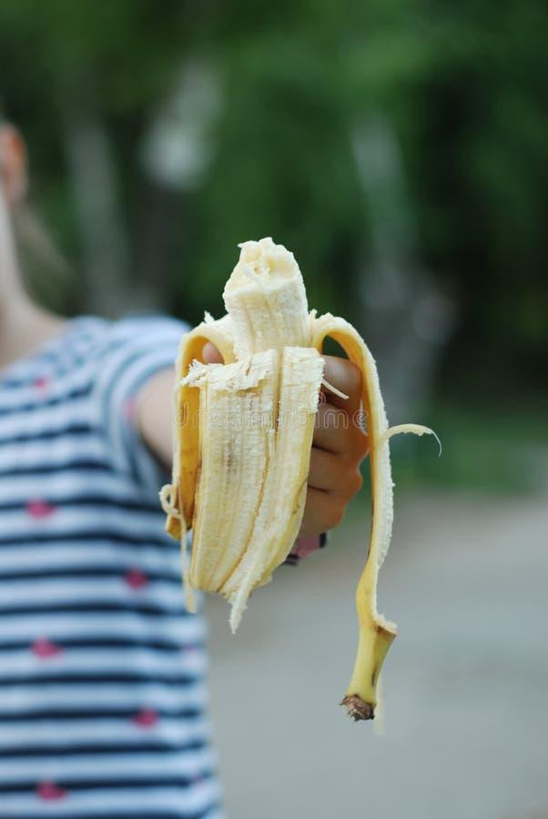 För bananmellanmål för liten flicka innehav skalad sund mat Eatting i den bildande matbarnuppfostran för parkera royaltyfria bilder