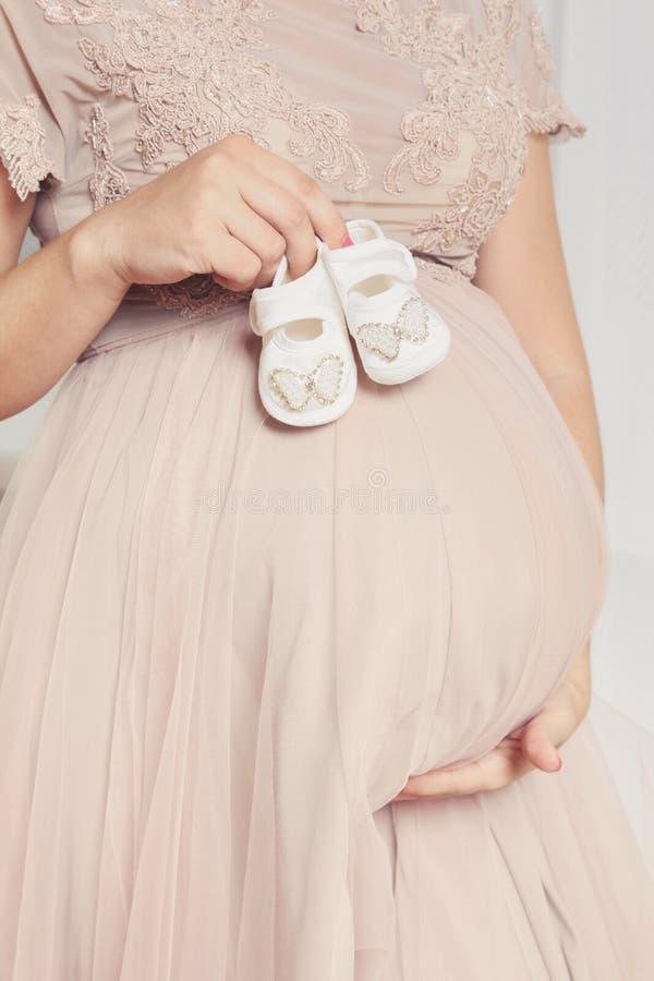 För barn` s för gravid kvinna hållande skor royaltyfria foton