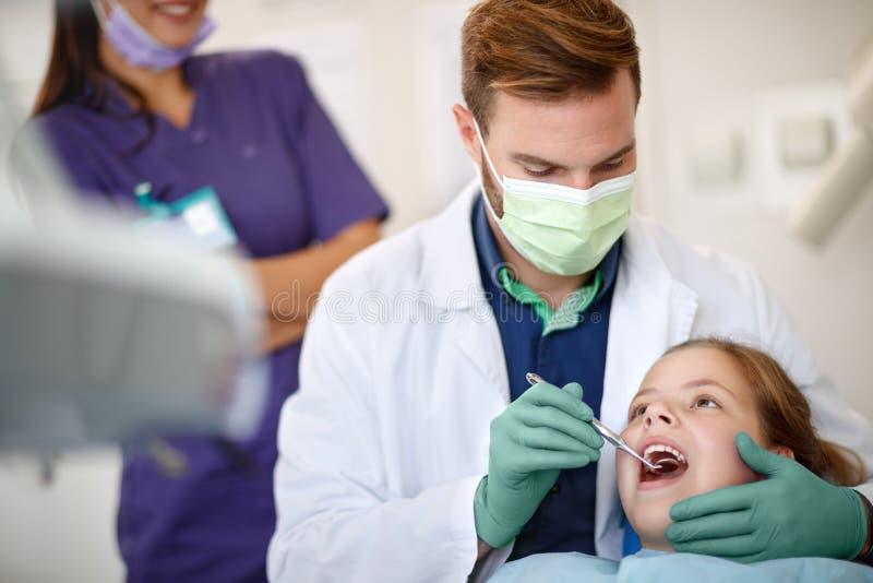 För barn` s för manlig tandläkare undersökande tänder med den tand- spegeln arkivbild