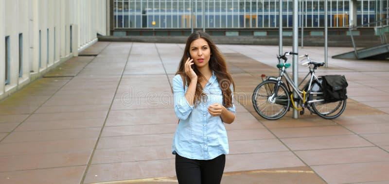 För barn som för entreprenöraffär tveksamt kvinna talar på mobiltelefonen utanför hennes kontorsbyggnad banerskörd för kopierings arkivfoton