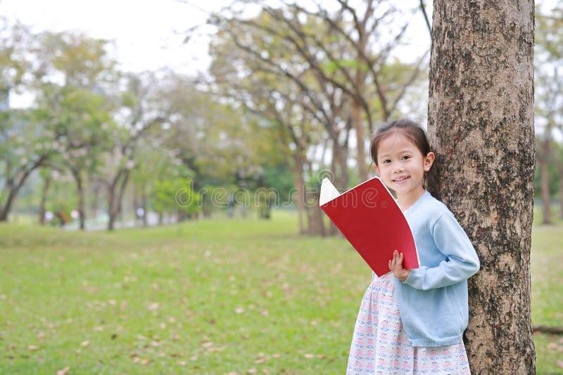 För barnflickan för ståenden parkerar den lilla asiatiska läseboken in utomhus- anseende lutar mot trädstammen med att se kameran royaltyfria foton