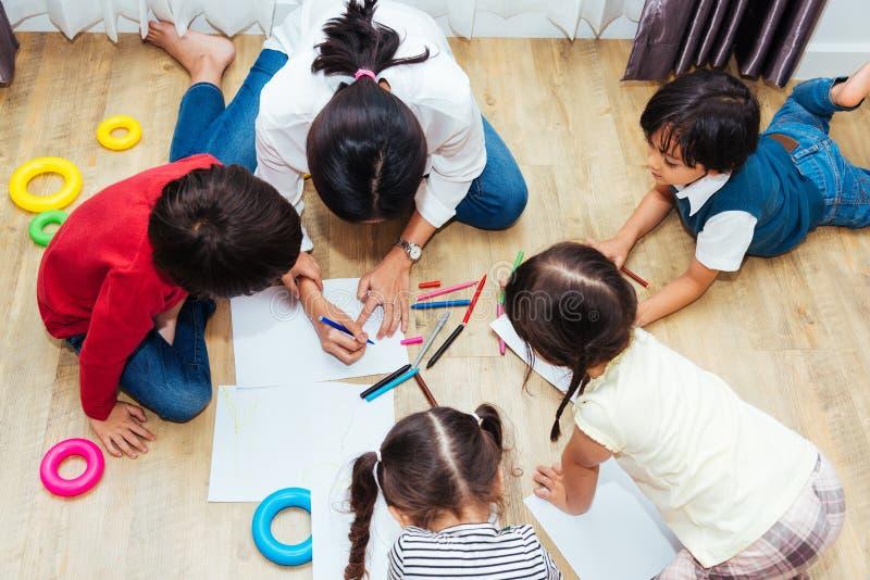 För barngrupp för familj lycklig teckning för målarfärg för dagis för pojke och för flicka för unge på peperlärareutbildning royaltyfria foton