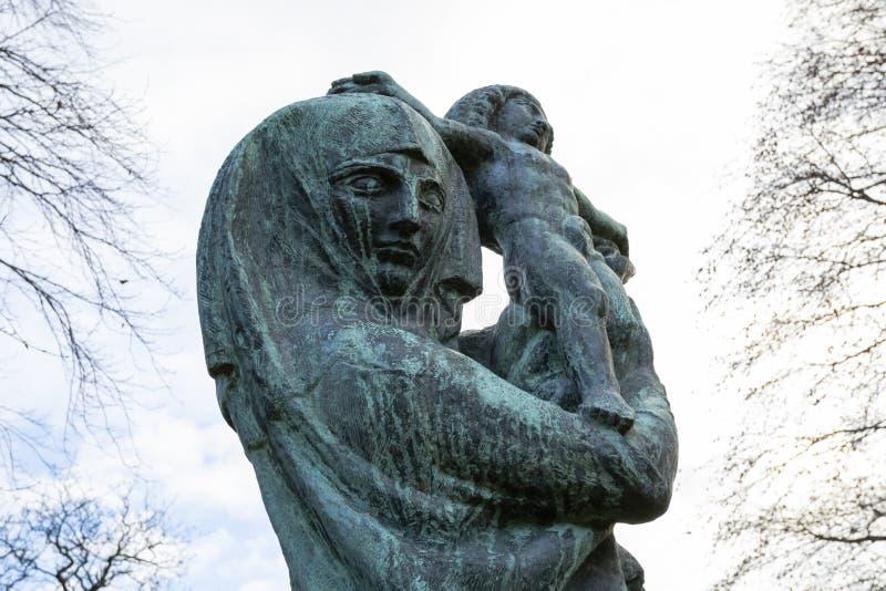 För barnstaty för kvinna hållande kyrkogård för dekan arkivfoton