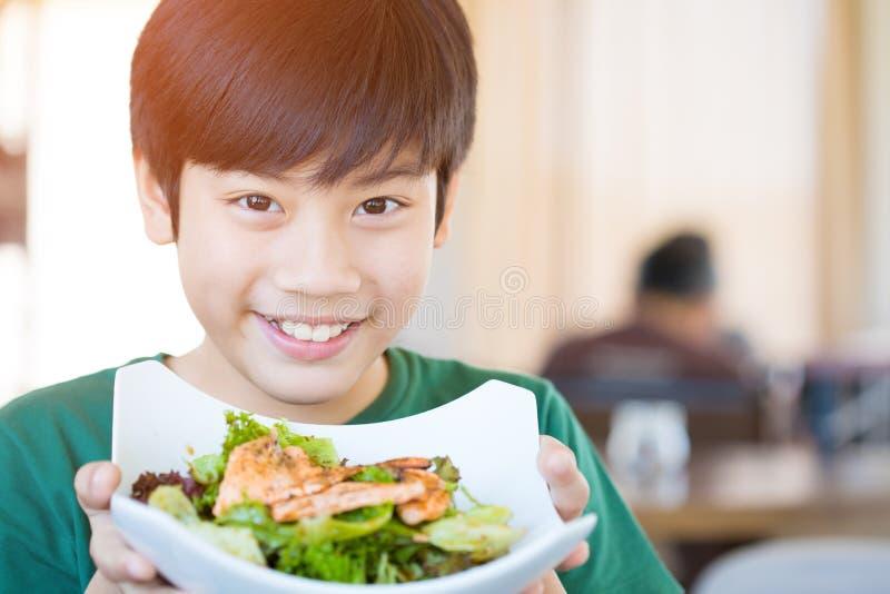 För barnvisning för sund livsstil asiatiskt le för sallad royaltyfria bilder