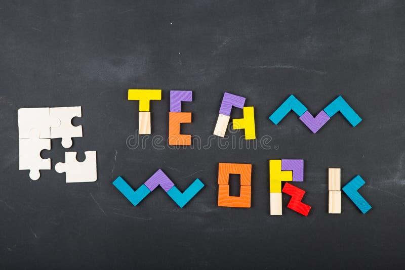 För begreppsbegrepp för teamwork idérik figursåg på svart tavla royaltyfria foton