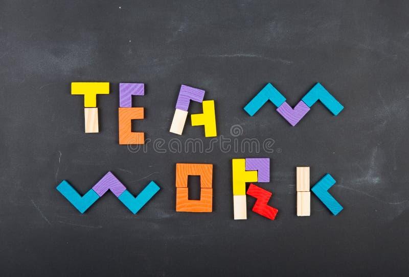 För begreppsbegrepp för teamwork idérik figursåg på svart tavla arkivbilder