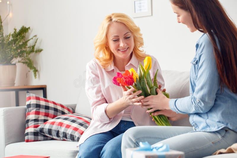 För berömsammanträde för moder som och för dotter tillsammans hemmastadd dotter ger blommor till att le för mamma som är lyckligt royaltyfri bild