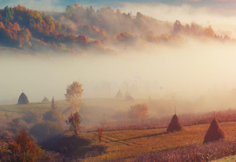 För bergkulle för bygd lantligt landskap med höstacken och morgondimma arkivbilder