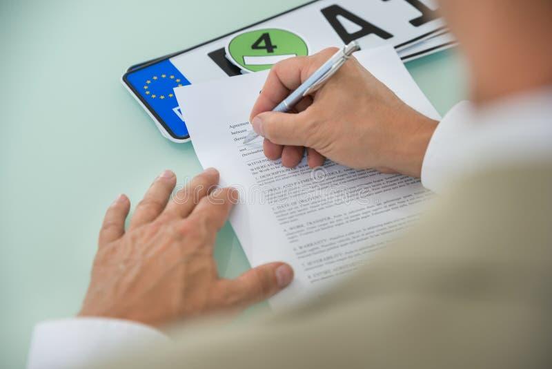 För bilförsäljning för affärsman fyllnads- form för avtal arkivfoto