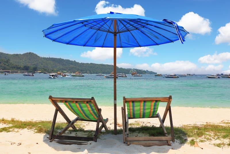 för blåa randigt paraply chaisevardagsrumar för strand arkivbilder