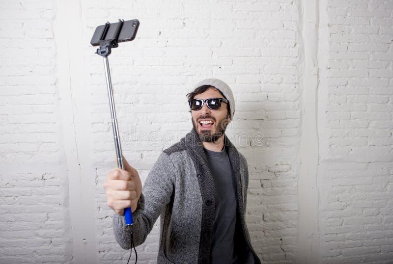 För bloggerman för ung hipster moderiktig video för selfie för inspelning för pinne för innehav i vlogbegrepp royaltyfria foton
