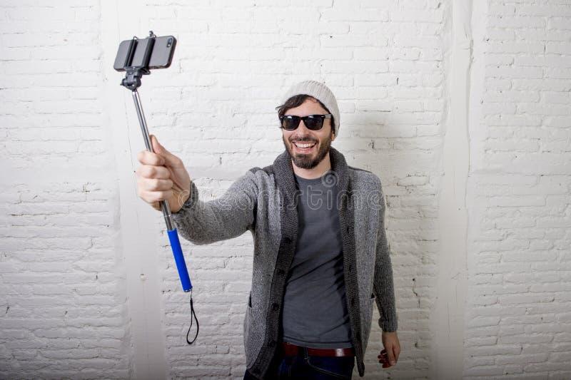 För bloggerman för ung hipster moderiktig video för selfie för inspelning för pinne för innehav i vlogbegrepp royaltyfria bilder