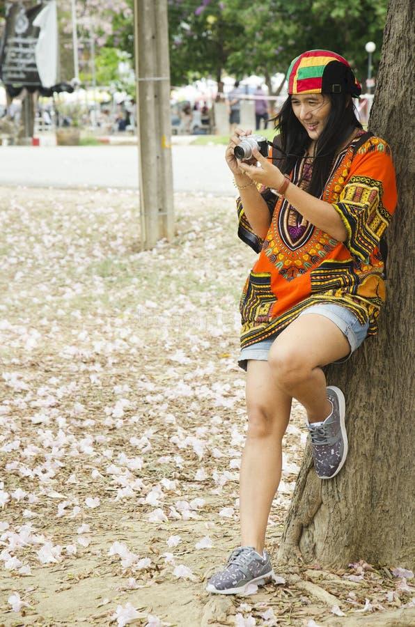 För bloggerskytte för asiatiska handelsresande thai foto med det rosa trumpetträdet arkivfoton