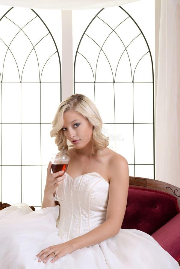 För bollklänning för kvinna bärande vitt hållande glass rött vin royaltyfri fotografi