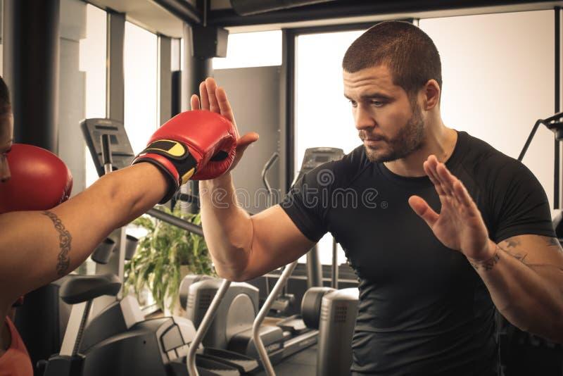 För boxningintelligens för ung kvinna instruktör Fokus på män royaltyfria bilder