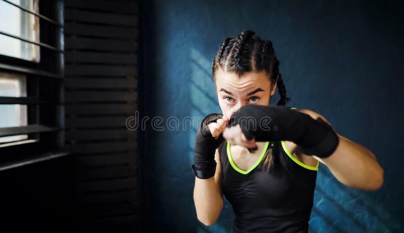 För boxningkvinna för stående som härlig ung utbildning stansar i fritt utrymme för idrottshall, copyspace royaltyfria foton