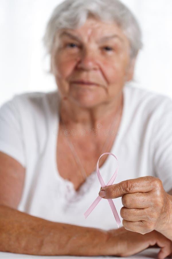 För bröstcancermedvetenhet för äldre kvinna hållande rosa band i hand royaltyfri bild