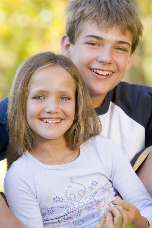 för broder le för syster utomhus sittande arkivfoton