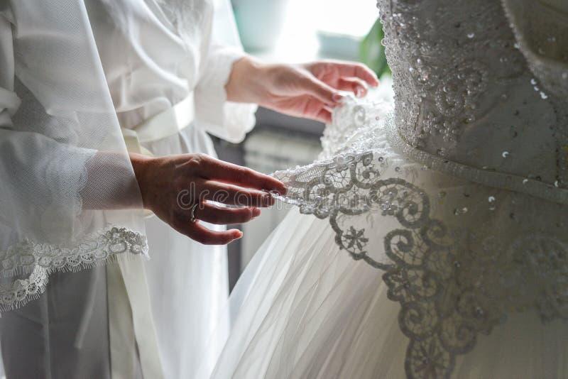 För brud` s för brudtärna hållande bröllopsklänning royaltyfri foto
