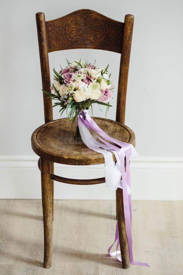 för brudbrudgum för bukett brud- händer Härligt av vita blommor och grönska, på tappningträstol arkivbilder