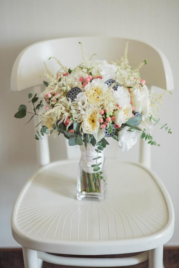 för brudbrudgum för bukett brud- händer Härligt av vita blommor och grönska, på tappningträstol arkivfoto