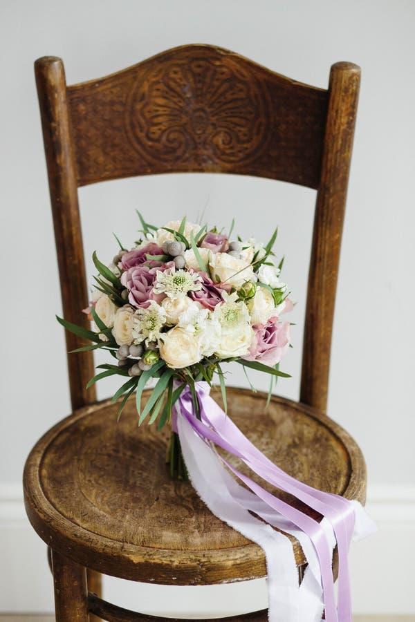 för brudbrudgum för bukett brud- händer Härligt av vita blommor och grönska, på tappningträstol royaltyfria foton