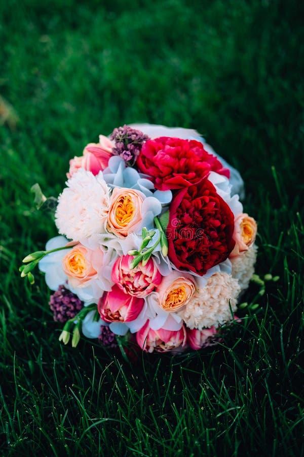 för brudbrudgum för bukett brud- händer Röda och vita pioner, freesia, rosor och lila royaltyfri bild