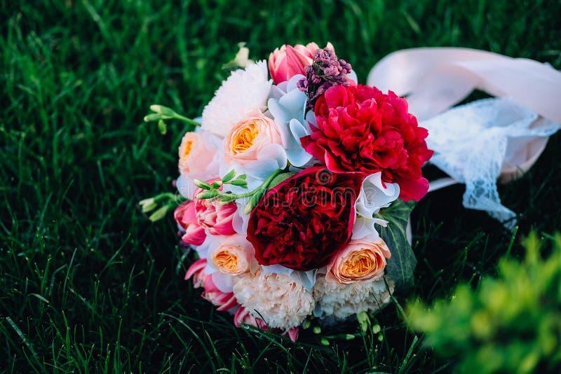 för brudbrudgum för bukett brud- händer Röda och vita pioner, freesia, rosor och lila arkivbild