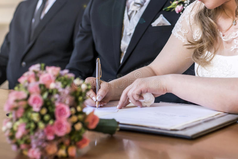 För brudunderteckning för förbindelse kopplar ihop det eleganta registret, den hållande pennan och bröllop för officiellt dokumen arkivbild